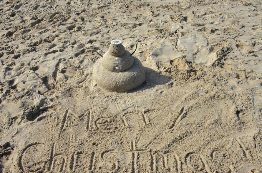 scritta merry christmas sulla spiaggia con pupazzo di sabbia