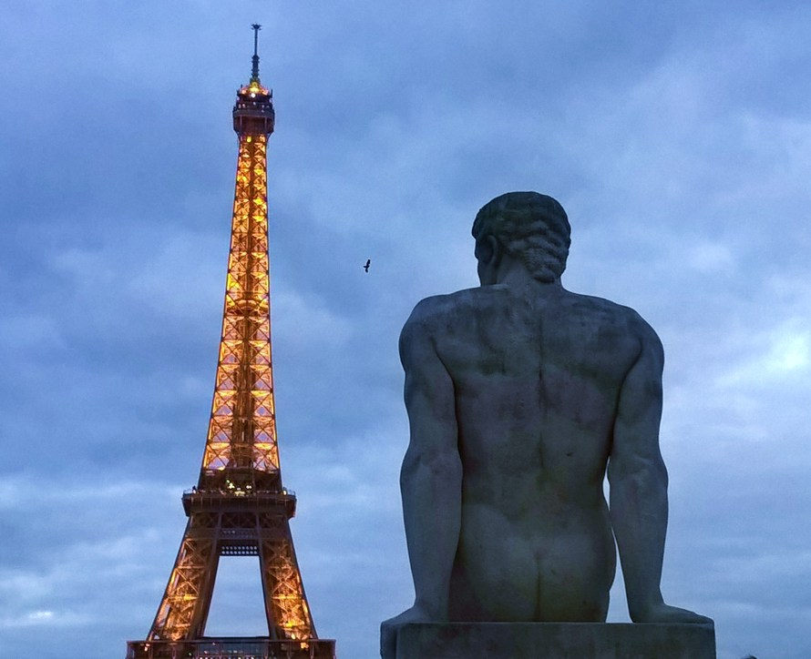 Tour Eiffel illuminata e una statua di spalle