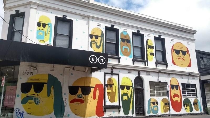 facciata di una casa dipinta con facce con occhiali da sole