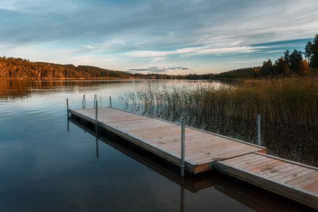 En brygga i en spegelblank sjö någonstans i Dalarna - Ludwig Sörmlind