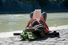 Near Ponte Regina Margherita. Along the bank a man is reading a book.