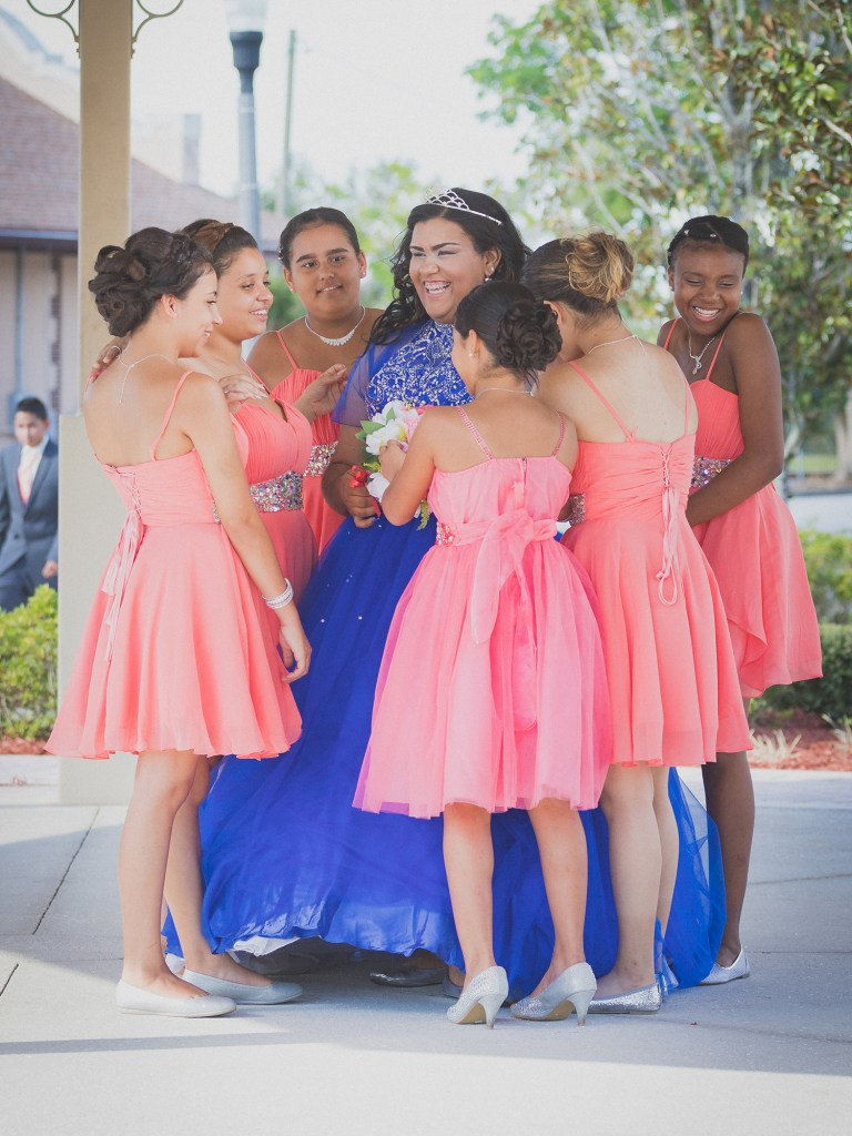 group of ladies or damas smiling with the quinceanera in blue dress and tiara luis betancourt photography