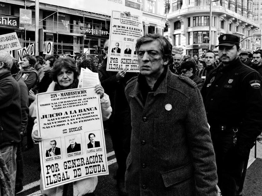 """Mujer con pancarta: """"JUICIO A LA BANCA. SALVEMOS LO PÚBLICO. SALVEMOS LAS MPENSIONES. SALVEMOS A LAS PERSONAS. SE BUSCAN: MIGUEL BLESA, DÍAZ FERRÁN, MORAL SANTÍN. POR GENERACIÓN ILEGAL DE DEUDA"""". Manifestación en Madrid contra los recortes del Partido Popular y el desmantelamiento del Estado de Bienestar en España. Fotografía de Luis F. Roncero."""