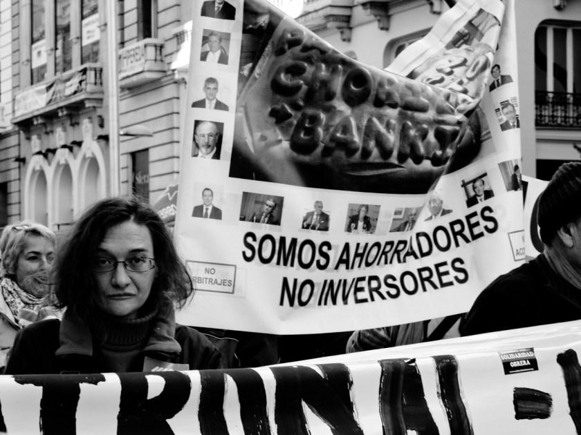 """Mujer tras una pancarta: """"Somos ahorradores, no inversores"""". Manifestación en Madrid contra los recortes del Partido Popular y el desmantelamiento del Estado de Bienestar en España. Fotografía de Luis F. Roncero."""