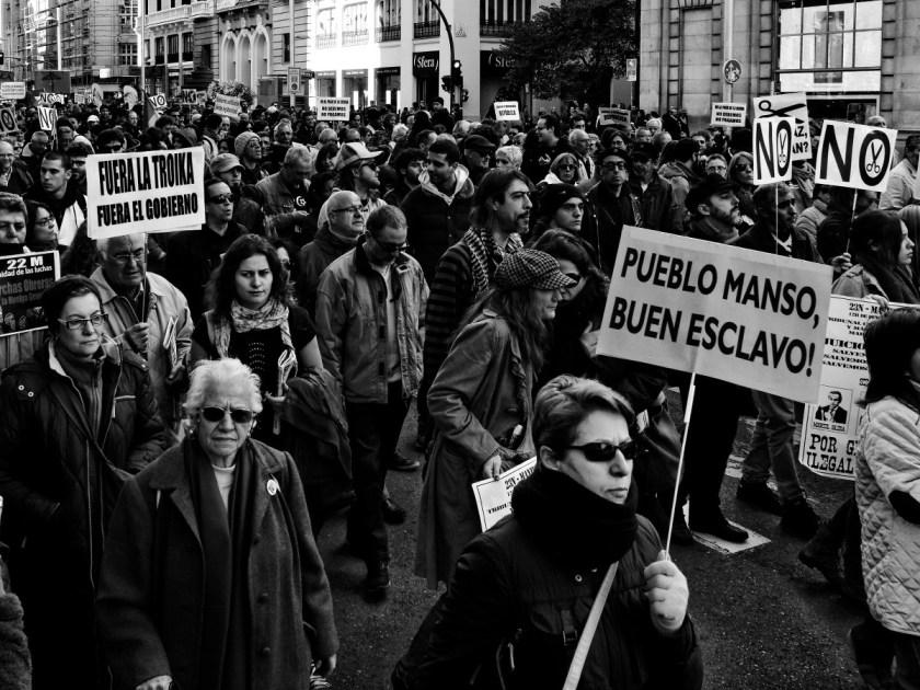 """Manifestantes con pancartas: """"FUERA LA TROIKA. FUERA EL GOBIERNO"""" Y """"PUEBLO MANSO, BUEN ESCLAVO"""". Manifestación en Madrid contra los recortes del Partido Popular y el desmantelamiento del Estado de Bienestar en España. Fotografía de Luis F. Roncero."""