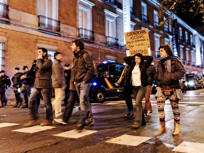Manifestantes pasando por delante de furgones policiales. Rodea el Congreso: manifestación en Madrid contra la Ley Mordaza del Partido Popular. Fotografía de Luis F. Roncero.