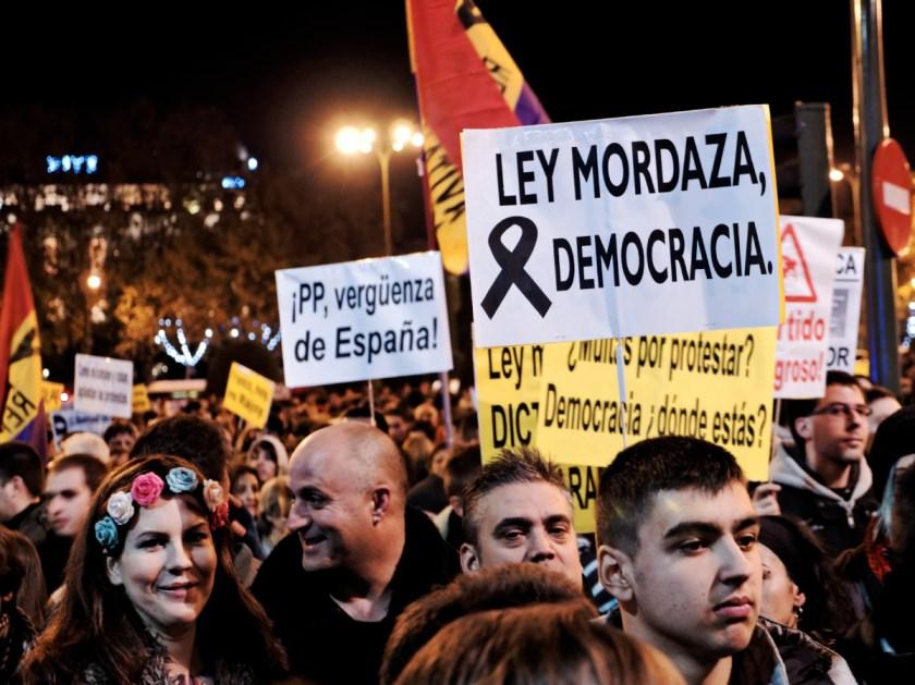 """Manifestantes con pancartas: """"LEY MORDAZA DEMOCRACIA"""" y """"¡PP, vergüenza de España"""". Rodea el Congreso: manifestación en Madrid contra la Ley Mordaza del Partido Popular. Fotografía de Luis F. Roncero."""