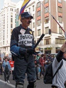 """Hombre disfrazado de policía con cartel de """"policía necional"""". Manifestación contra la Ley Mordaza del Partido Popular en Madrid. By Luis F. Roncero"""