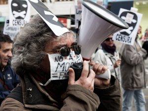 Manifestante con máscara y megáfono con pancartas contra la censura de fondo. Manifestación contra la Ley Mordaza en Madrid. By Luis F. Roncero