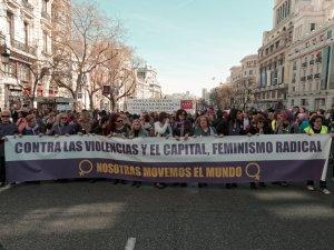 """Mujeres sostienen pancarta: """"Contra las violencias y el capital, feminismo radica. Nosotras movemos el mundol"""". Manifestación el Día Internacional de la Mujer en Madrid. By Luis F. Roncero"""