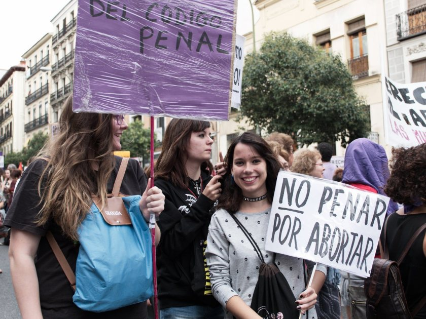 """Chica joven con pancarta contra la penalización del aborto: """"NO PENAR POR ABORTAR"""". Manifestación en Madrid contra la reforma de la ley del aborto del Partido Popular. Fotografía de Luis F. Roncero."""
