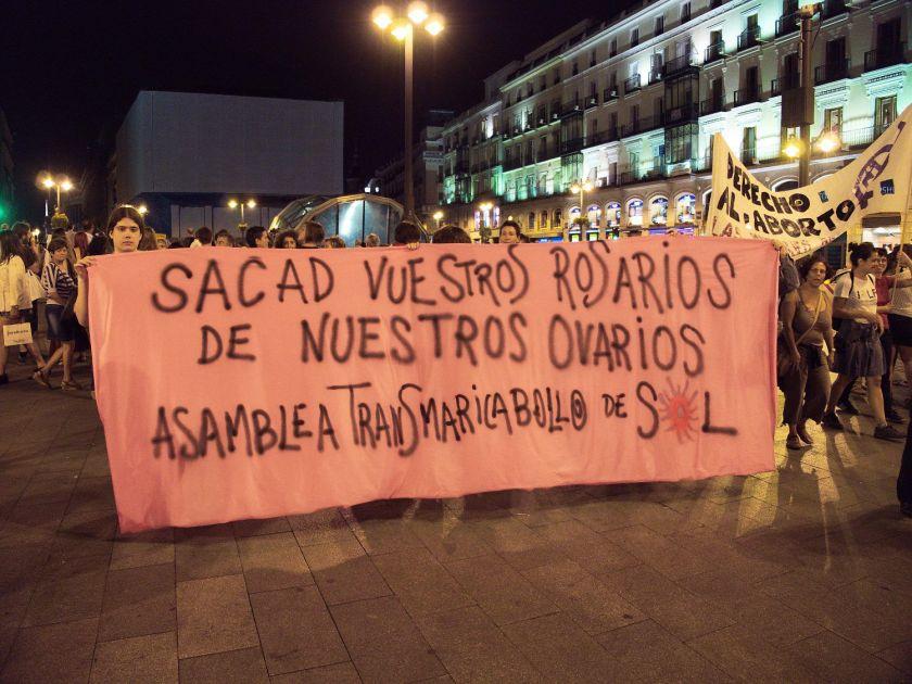 """Pancarta """"Sacad vuestros rosarios de nuestros ovarios"""" en la Puerta del Sol de Madrid. Manifestación en Madrid contra la reforma de la ley del aborto del Partido Popular. Fotografía de Luis F. Roncero."""