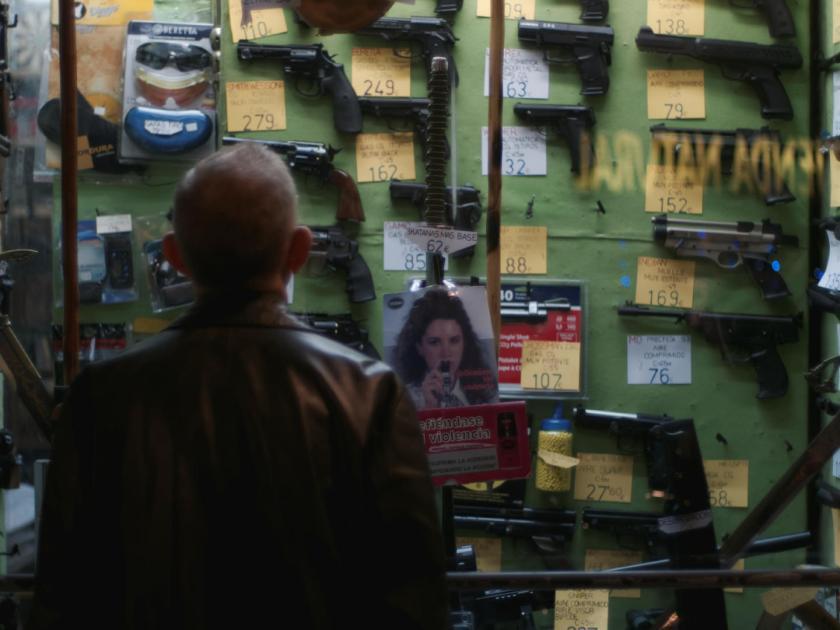 Hombre de espaldas mirando escaparate con réplicas de armas de fuego. Fotógrafo: Luis F. Roncero.
