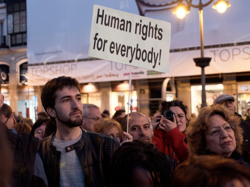 """Chico con barba sostiene pancarta por los derechos humanos: """"Human rights for everybody!"""" Manifestación por los derechos de los refugiados en la Puerta del Sol de Madrid. Fotografía de Luis F. Roncero."""