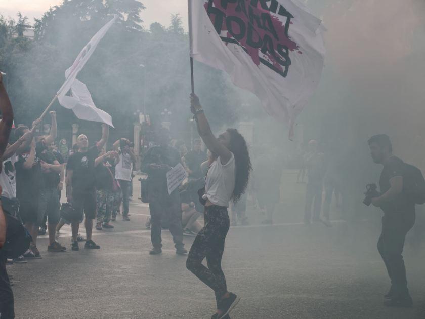 """Chica rodeada de humo ondea bandera en cabecera de manifestación. """"Madrid para todas"""" Manifestación antifascista contra la discriminación, el racismo y el Hogar Social de Madrid. Fotografía de Luis F. Roncero."""