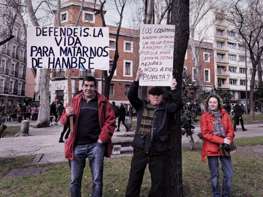 """Hombres sostienen pancarta pro-choice: """"Defendéis la vida para matarnos de hambre"""". El Tren de la Libertad. Manifestación contra la Ley Gallardón del Partido Popular. Fotografía de Luis F. Roncero."""