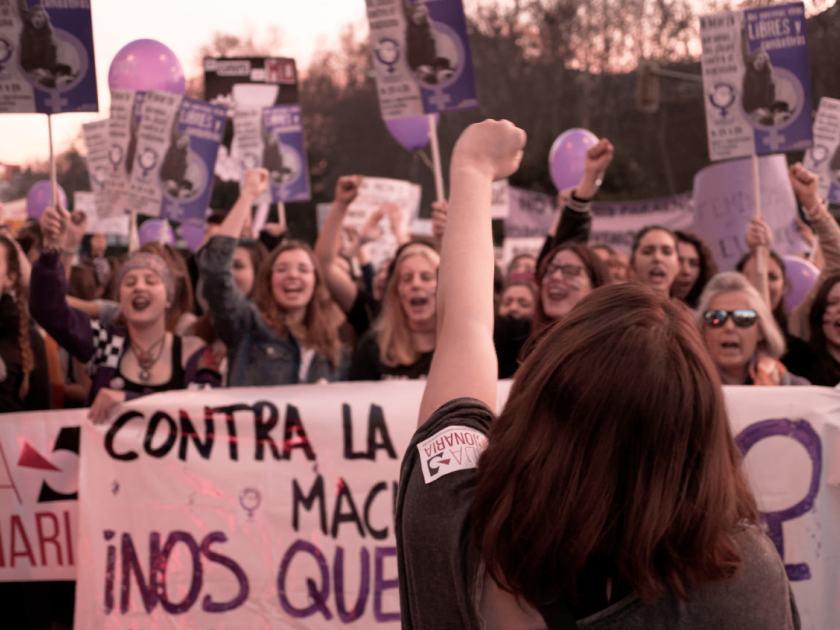 Feminista con el puño en alto anima a grupo de manifestantes. Manifestación del Día Internacional de la Mujer en Madrid. Fotografía de Luis F. Roncero.