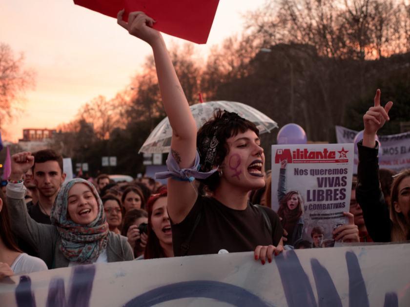 Mujeres con el puño en alto tras una pancarta. Manifestación del Día Internacional de la Mujer en Madrid. Fotografía de Luis F. Roncero.