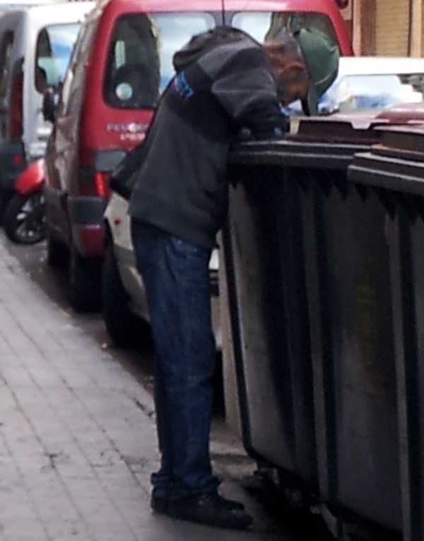 Man searching for food in a garbage dumpster