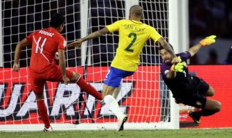 Peru's Raul Ruidiaz (11) scores a goal past Brazil's goalkeeper Alisson, right, and Dani Alves (2) in the second half of a Copa America Group B soccer match on Sunday, June 12, 2016, in Foxborough, Mass. (AP Photo/Steven Senne)
