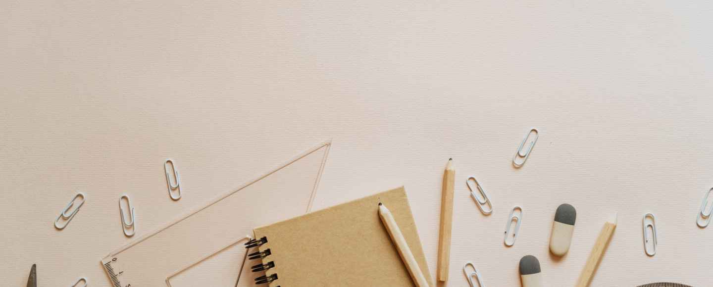 spiral notebook pencils and paper clips flatlay
