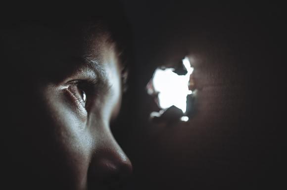 Pessoa espia através de um buraco na parede