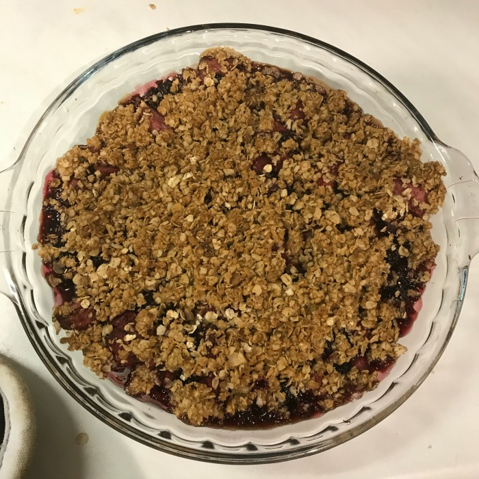 Aerial view of a black berry and apple crumble in a pie dish.