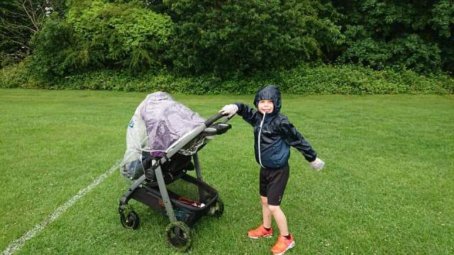 A boy smiling at the camera as he pushes a baby along in the buggy in the rain