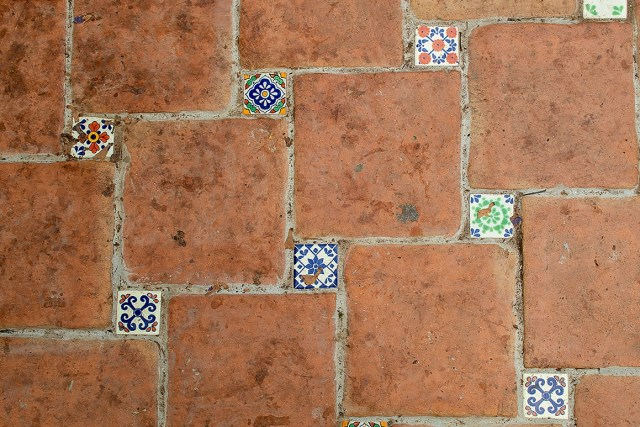 the paving on the floor of the Mediterranean biome at the eden project, it features a pattern of large terracotta tiles and smaller, colourful patterned tiles.