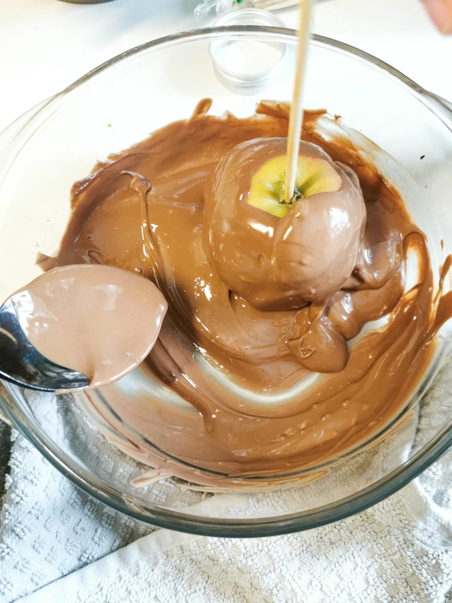 An apple being dipped in chocolate. The side is being covered with chocolate by using a spoon.
