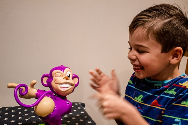 A child laughing in delight as Mr Buster the purple monkey from the Pull My Finger game farts.