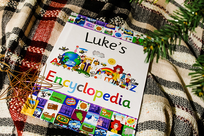 Personalised children's encyclopedia underneath a Christmas tree.