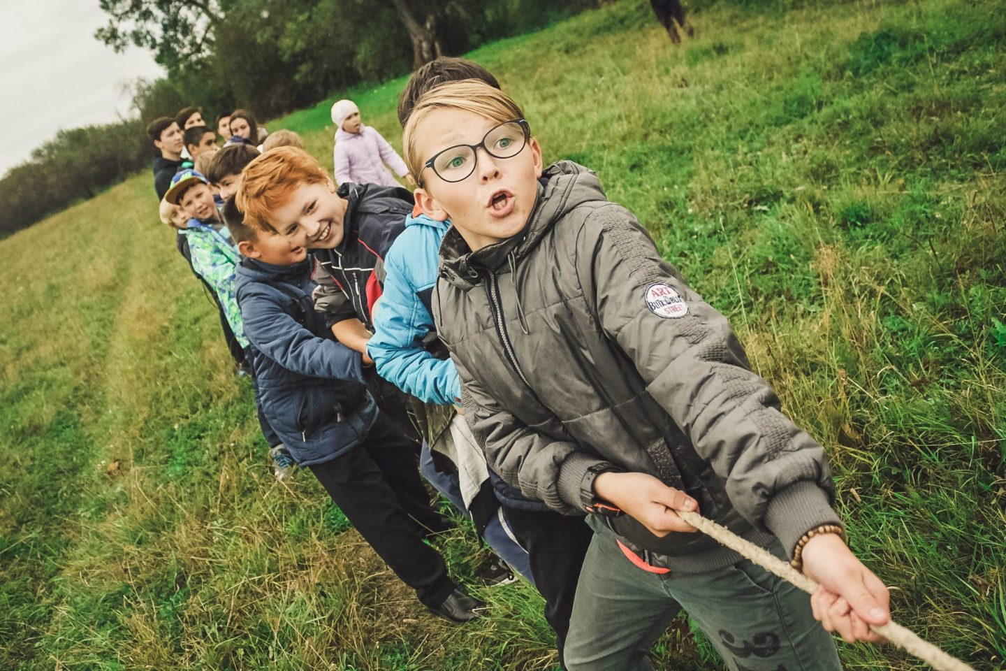 Children playing tug of war in a field for a blog post on Helping Your Child Develop Social Skills at https://lukeosaurusandme.co.uk