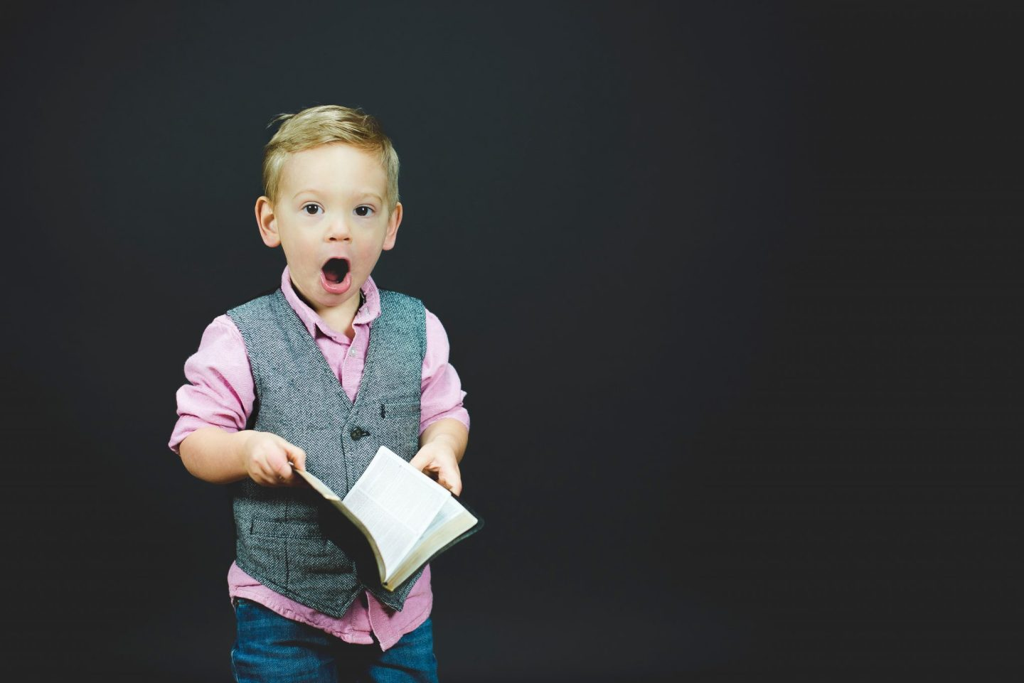 Boy wearing a pink shirt and grey waistcoat, holding a book with a shocked expression. For a blog post on balancing school and home life at https://lukeosaurusandme.co.uk