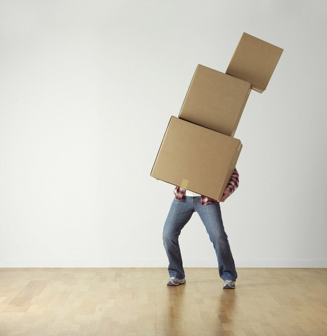 A man holding a pile of cardboard boxes that are falling over for a blog post about moving house.