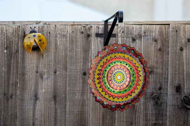 A yellow ladybird solar light on a fence with a mandala wind chime hanging from a bracket on the fence. For a post on making your rented garden look beautiful.