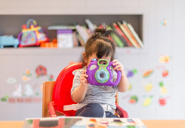 Girl looking through a toy camera with other toys and books in the background