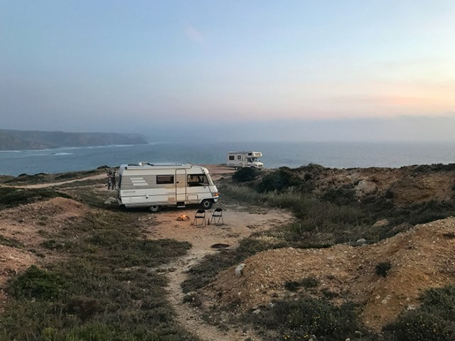 Motorhome on a cliff top with 2 chairs and a fire pit outside. For a blog post on campervan and motorhome holidays in the UK.