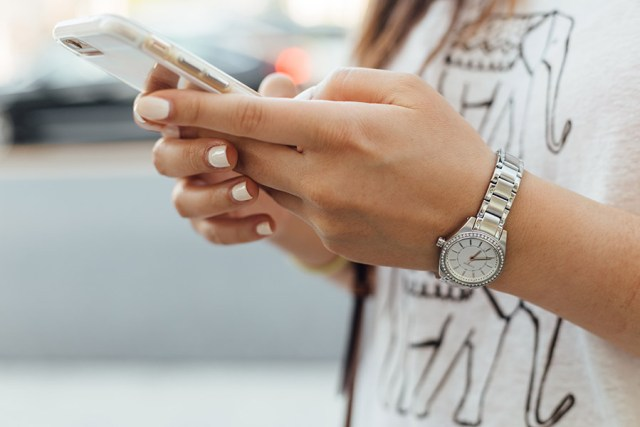 Woman with pale pink painted nails, a silver watch and a white t shirt with elephants on it holding her mobile phone as if shes texting. For a blog post on sexting in teenagers and the things you need to watch out for.