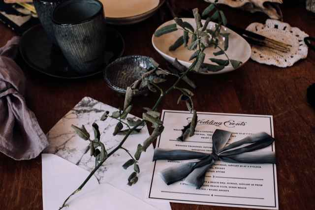 wedding invitation on table with utensil and decorations