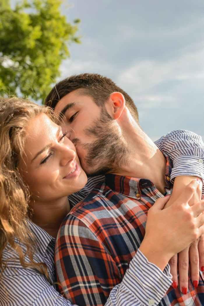 man kissing woman