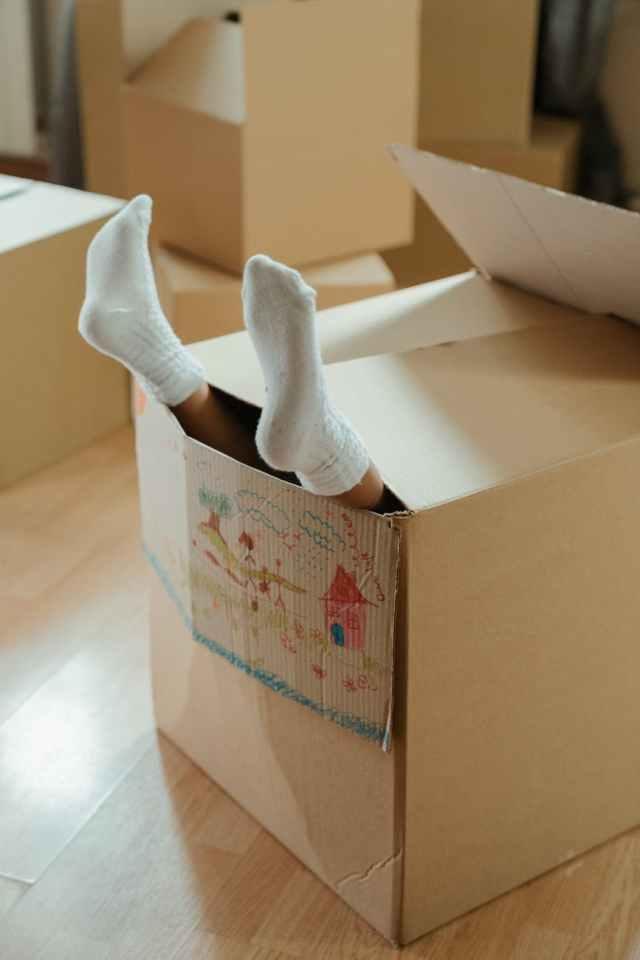 person wearing white socks on brown cardboard box