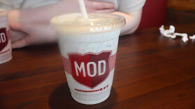 A white and red MOD Pizza plastic cup on a brown wooden table.