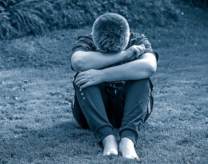 Sad teenager hiding his face