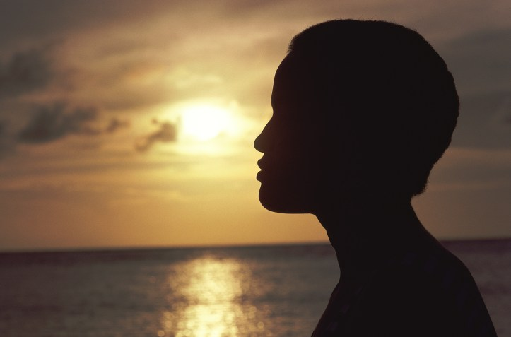 Silhouette of young person looking to the horizon