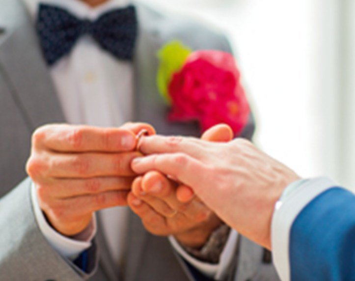 A close-up of a male's hands placing a wedding ring onto the finger of another male.