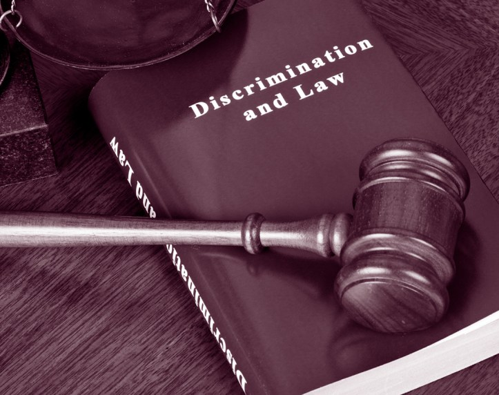 A gavel laying across a Discrimination and Law handbook