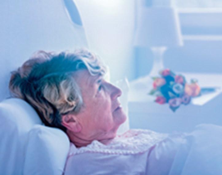 Elderly woman lying in a hospital bed.