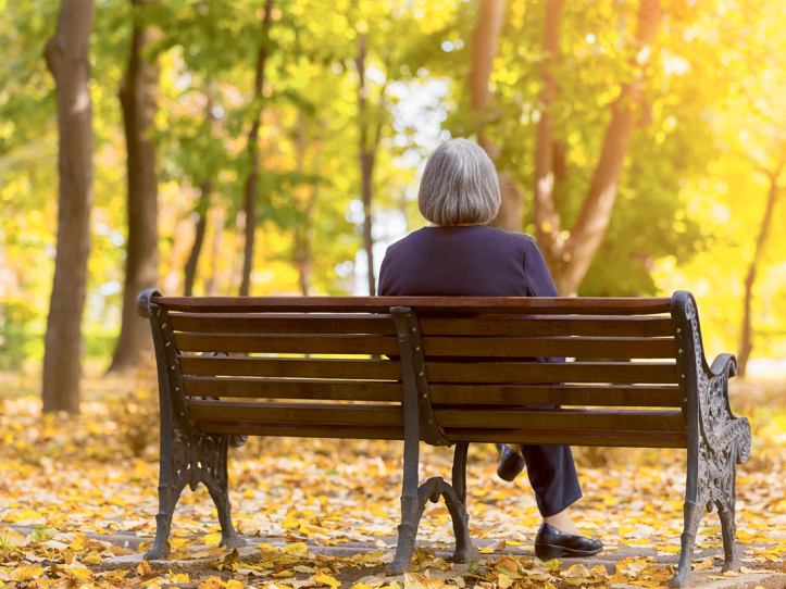 Aged woman sitting on a park bench in Autumn
