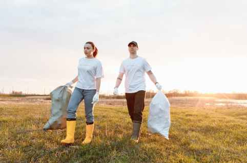 a man and a woman holding sacks of garbage